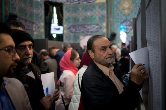 2月21日,在伊朗首都德黑兰,人们在一处投票站参加议会选举投票
