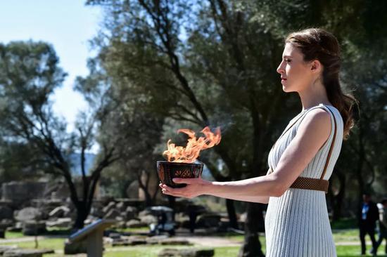 3月12日,2020東京奧運會聖火採集儀式在希臘古奧林匹亞舉行,扮演女祭司的演員在聖火採集儀式上手捧點燃的火種罐