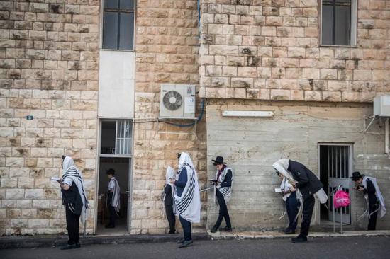 在犹太会堂外祈祷的犹太人,根据防疫规定保持着大约两米的距离 摄影|<img src=
