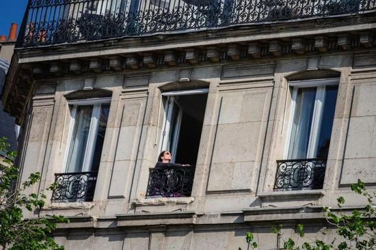 2020年4月13日,在法国巴黎西岱岛,一名女子在窗边晒太阳。(新华社发)
