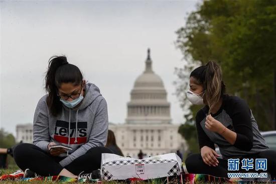 ▲4月19日,在美国首都华盛顿,两名戴口罩的女子坐在国家广场草坪上。新华社发(沈霆 摄)