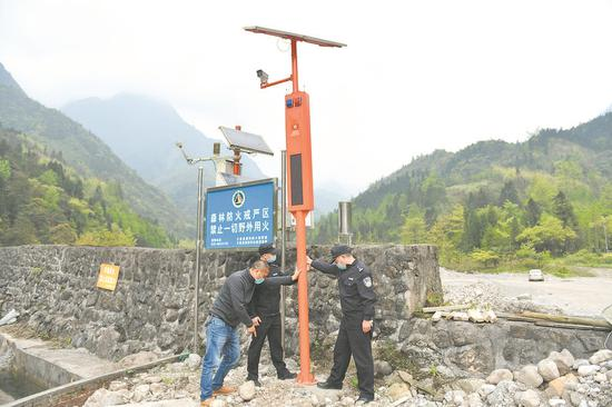 周波(右一)和队友检察丛林防火监控装备