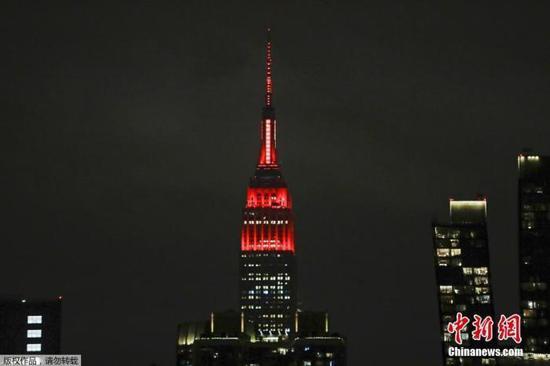 当地时间3月31日,美国纽约帝国大厦点亮红色和白色灯光致敬医疗工作者。