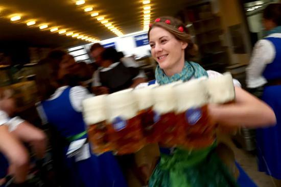 2019年9月21日,在德国慕尼黑,服务员在啤酒节上准备向人们分发啤酒。新华社/美联