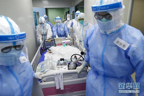4月24日,武汉协和医院的医护职员将患者转运至手术室。(泉源:新华网)