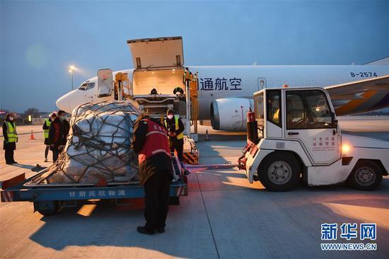 2月19日,在兰州中川国际机场,机场货运事情职员往飞机上装运运往武汉的防疫物资。 新华社记者 范培珅 摄