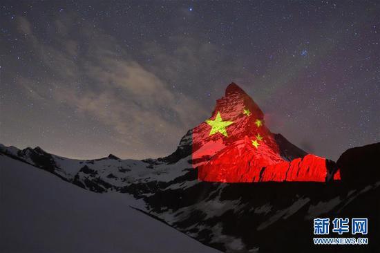 4月19日,瑞士采尔马特市旅游局用灯光将一面五星红旗投射到四周阿尔卑斯山脉的马特洪峰。 新华社发(瑞士采尔马特市旅游局供图)