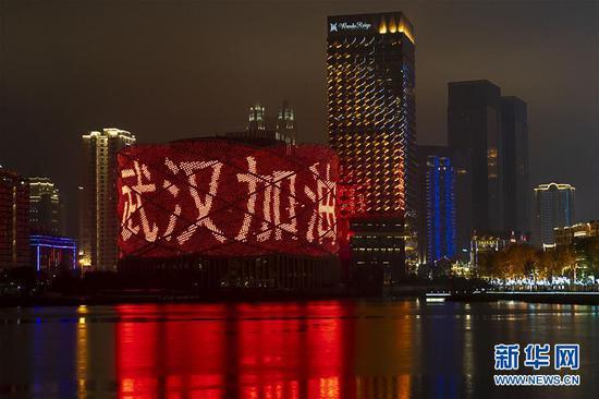 """1月24日是除夕,湖北省武汉市汉秀剧场的外墙打出""""武汉加油""""字样。 新华社记者 熊琦 摄"""
