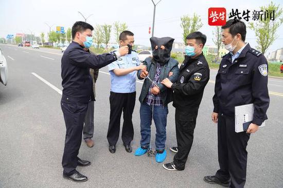 警方押着嫌犯指认当年作案现场。