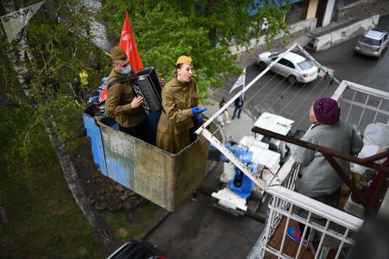 5月9日胜利日时,俄罗斯一些小区用起重机把演员送到老兵的窗外,进行演奏。今日俄罗斯图