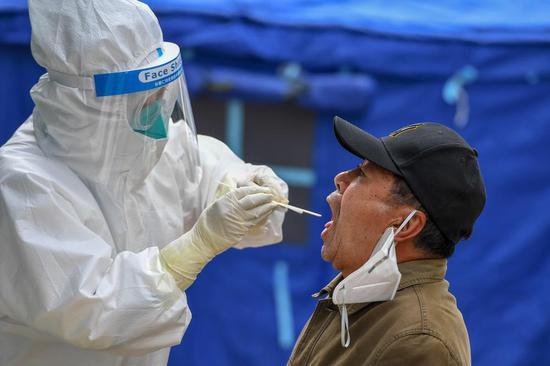 5月15日,在舒兰市建馨园小区,事情职员为住民收罗咽拭子。