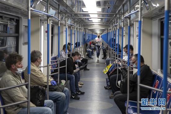 5月12日,在俄罗斯首都莫斯科,人们佩戴口罩乘坐地铁(图/新华社)