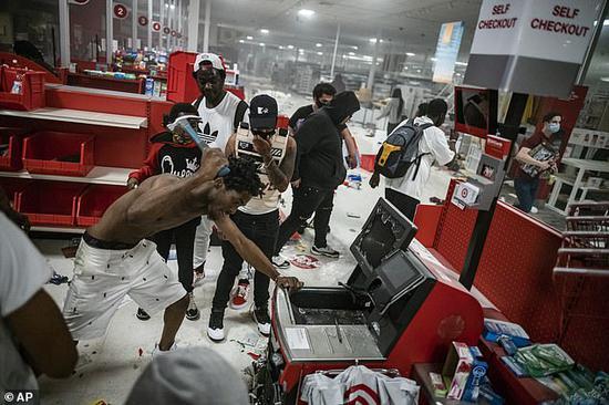 27日,示威者打砸抢劫明尼亚波利斯市一家超市。(美联社)