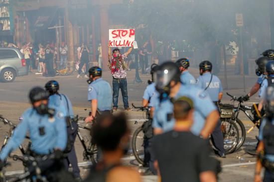 27日,明尼阿波利斯一名示威者与警察对峙(路透社)