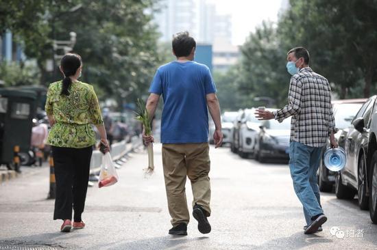 △6月20日,西城區樂城社區,居民買完生活必需品,邊走路邊聊天回家。