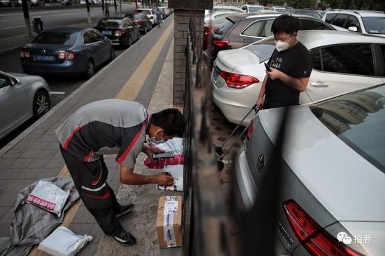 △6月20日,西城區樂城社區,隔著小區欄桿,快遞員為居民尋找快遞。