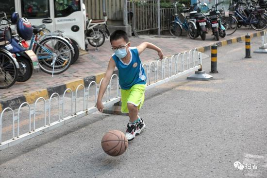 △6月20日,戴著口罩練球的男孩。封閉的小區少了車來車往,路上也能成為運動場。