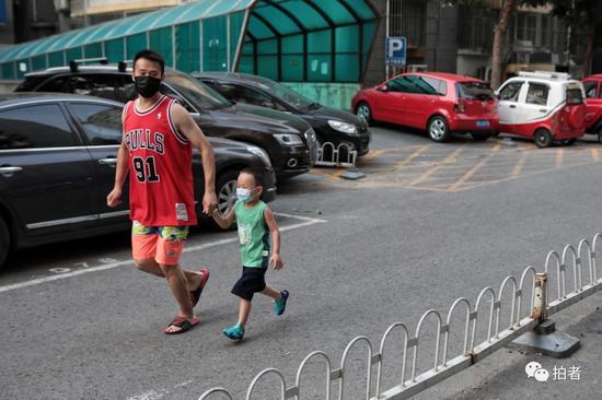 △6月20日,西城區樂城社區,家長牽著小朋友在小區內跑步鍛煉。