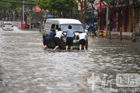 △7月2日,世人将熄火汽车推离积水路段。当日,昆明降雨连续,市区多地泛起淹积水,给市民出行带来未便。中新社记者 刘冉阳 摄