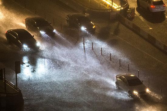 2020年7月2日晚9点,杭州大雨滂湃,中河高架上车辆驶过溅起伟大水花,开车如行舟。人民视觉 图