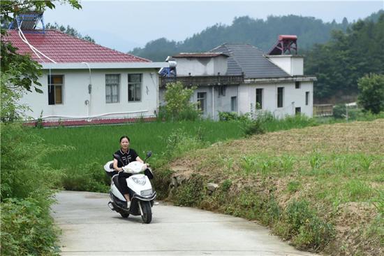 在安徽省岳西县来榜镇公山村,汪链骑车出行事情(6月24日摄)。新华社记者 周牧 摄