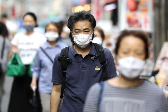 7月5日,在日本东京,人们戴口罩出行。新华社记者 杜潇逸 摄
