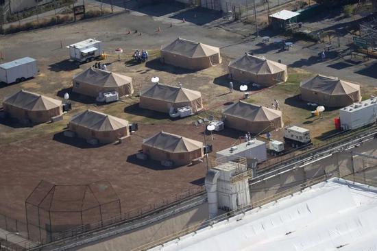 (图说:圣昆廷监狱后院用于安置感染新冠囚犯的帐篷。)