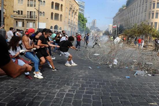 示威者拉开铁丝网试图冲入黎巴嫩议会大楼(图源:新华社)