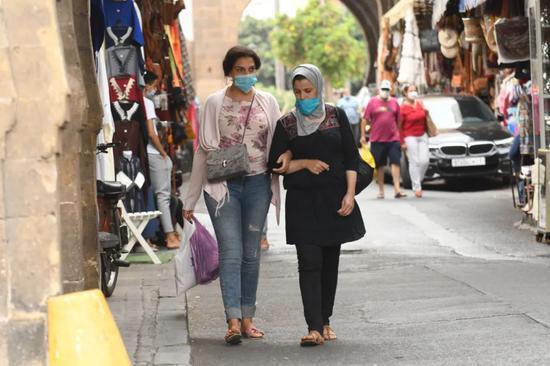 这是9月16日在摩洛哥卡萨布兰卡街头拍摄的戴口罩的行人。新华社发(查迪 摄)