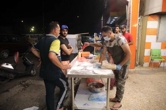 9月12日,伊拉克巴格达一家餐馆的工作人员在准备食物。新华社发(哈利勒·达伍德摄)