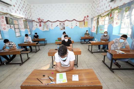 9月1日,在伊拉克巴格达,高中生佩戴口罩参加考试。新华社发