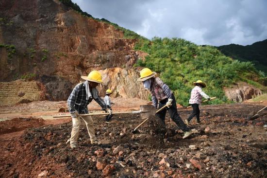 在大宝山,施工人员对土壤进行施肥改造(8月4日摄)。本报记者邓华摄