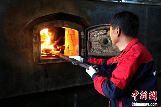 工人查看锅炉内煤炭燃烧情况。 王平 摄