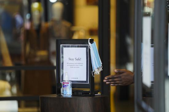 美国纽约一家商店的入口处摆放着为顾客准备的防疫物品。新华社图