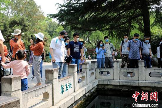 资料图:游客在山东济南漱玉泉畔观泉。李欣 摄