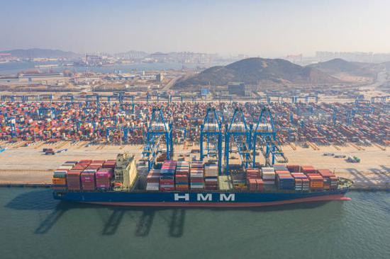2021年2月21日,航拍青岛港忙碌的船埠,集装箱分列成行,货轮装载满满 图源:视觉中国