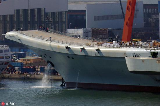 4月20日,工人在用高压水枪冲洗甲板,可见国产航母的球鼻艏已经完全没入海中(图片来源:东方IC)