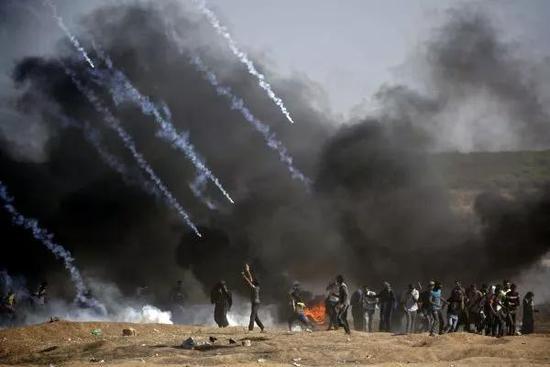 ▲5月14日,在加沙地带与以色列接壤的边境地区,巴勒斯坦抗议者在示威活动中躲避以军的催泪弹。(新华社/法新社)