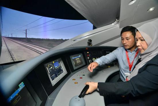 2017年1月16日,在马来西亚吉隆坡,人们体验中国高铁列车控制台模型。 新华社发(张纹综摄)