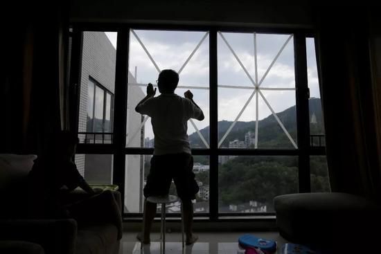 """△15日,深圳,超强台风""""山竹""""即将来袭,当地民众在窗户上贴满胶带,防止玻璃碎裂伤人。(图自视觉中国)"""
