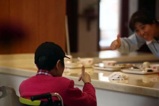 失智照料中心的护工与81岁阿尔茨海默症患者互动