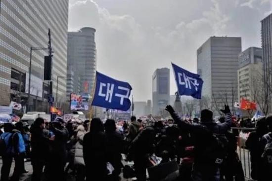 """参加集会的大邱市民手持""""大邱""""手牌(图源:韩媒)"""