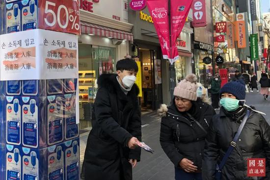 (资料图)2月8日,在首尔明洞地区,销售人员和到访游客大多佩戴口罩。中新社记者 曾鼐 摄