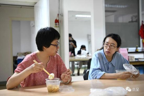 杨会娟(左)与同事曹丽娜一边吃早饭一边接头事情