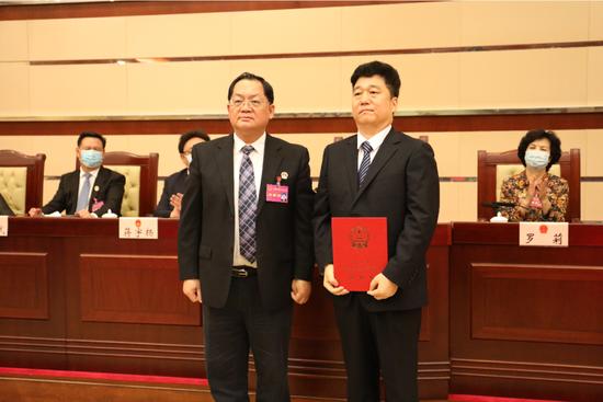 ▲深圳市人大常委会主任骆文智(左)为刘国周颁发任命书。
