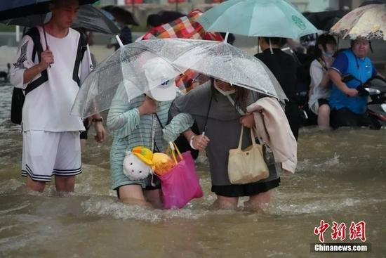 7月20日,河南郑州暴雨成灾。图为市民相互搀扶穿过积水的马路。中新社记者 李超庆 摄