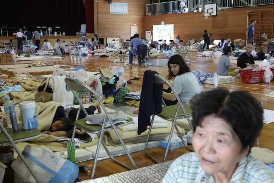 7月9日,在日本冈山县仓敷市,居民在避难所休息。新华社/法新