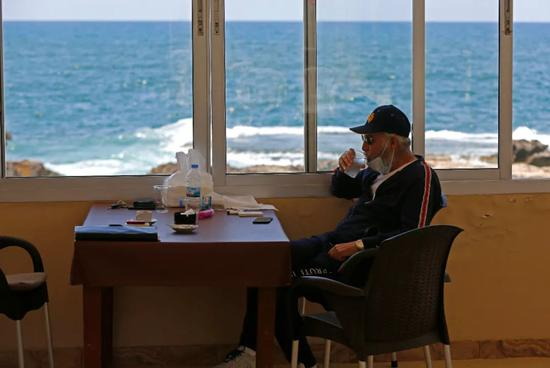 5月4日,一名男子在黎巴嫩贝鲁特一家餐馆内准备就餐。新华社发(比拉尔·贾维希摄)