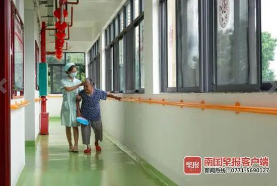 ▲广西重阳老年公寓万力分院内,护理人员搀扶老人在走廊行走。