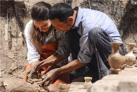"""在喀什老城一户参与""""石榴籽方案""""体验游项目的土陶匠人家中,意大利游客劳拉(左)在土陶匠人吐尔逊·祖农的协助下给泥胚塑型(5月18日摄)新华社记者马锴摄"""